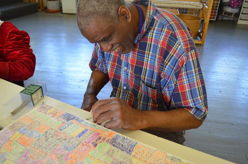 Sidney Perry working on a drawing on clay board in 2014.